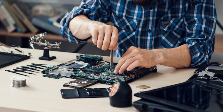 Homem mexendo em placa de hardware