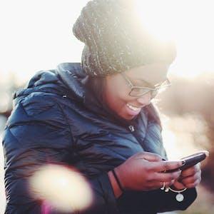 jovem sorridente usa telefone com plano tim black