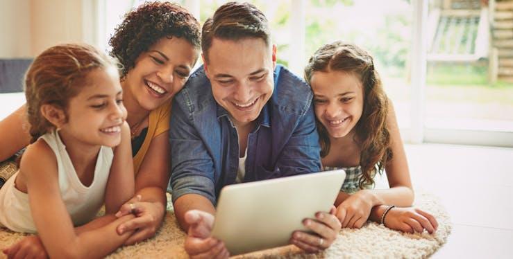 Família feliz assistindo em um tablet