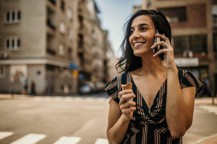 Mulher andando na rua, tomando sorvete e falando ao celular