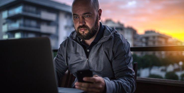 Homem configurando internet no notebook e celular