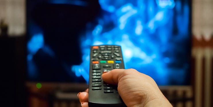 Pessoa segurando o controle de televisão