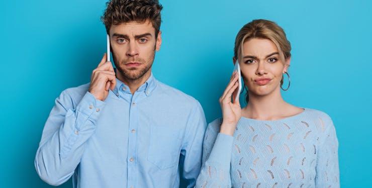 Homem e mulher falando no celular com expressão de insatisfação.