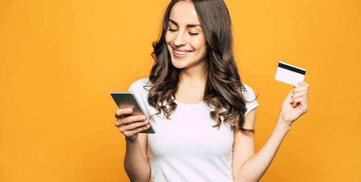 Mulher com celular e cartão de crédito em mãos.