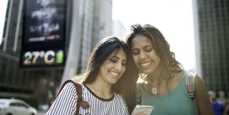 Duas mulheres olhando para celular