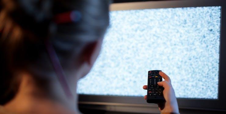 Mulher tentando configurar a TV sem funcionamento