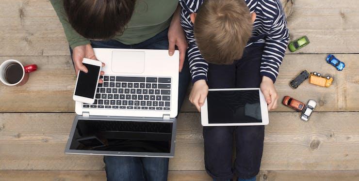 Mãe e filho utilizando conectados no tablet e notebook.