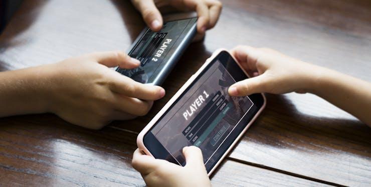Duas pessoas com jogo online aberto no celular
