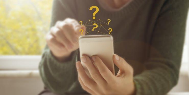 Pessoa segura celular que está com interrogações saindo da tela, simbolizando FAQ