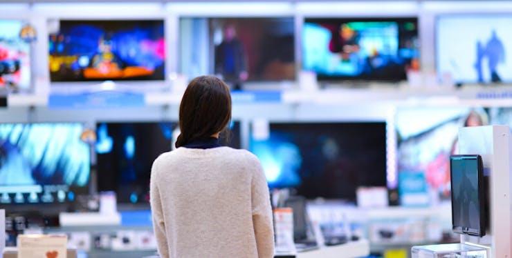 IPTV: mulher de costas observa vários televisores