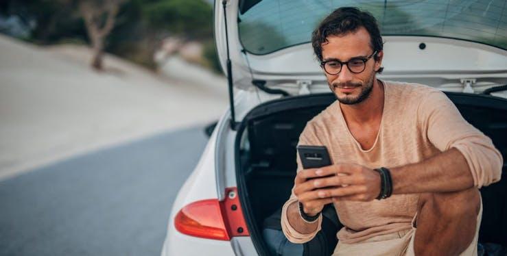 Homem sentando no carro olhando para o celular