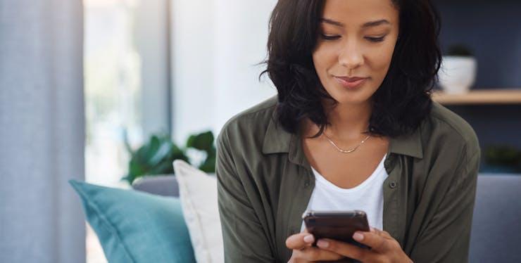 Imagem mulher mexendo no celular para descobrir o código da Oi