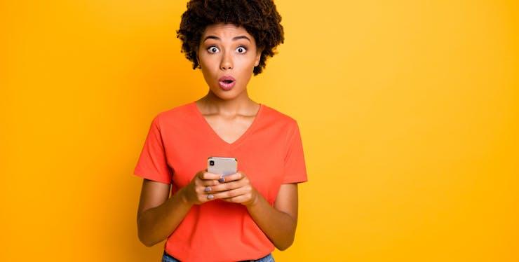 Mulher com expressão de surpresa vendo o celular