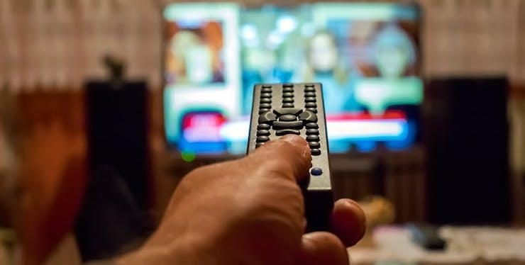 TV por Assinatura: pessoa com controle remoto apontando pra TV