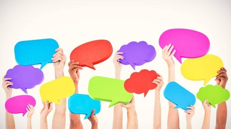 Mãos segurando balões de fala colorido