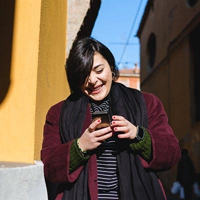 mulher sorridente utiliza plano tim pós-pago