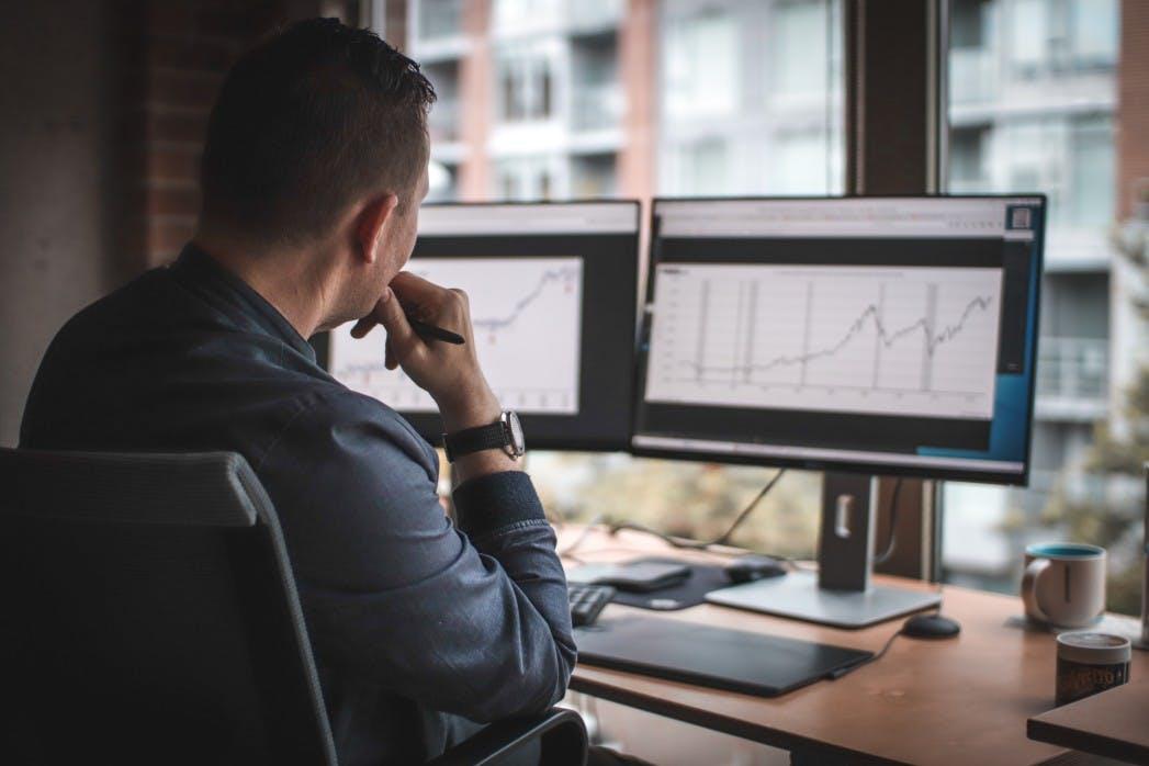 Trader profissional olhando gráficos da bolsa de valores