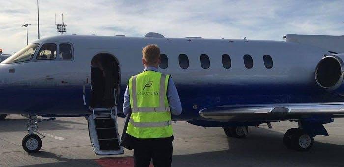 Agent avec un gilet jaune PrivateFly devant un avion sur la piste d'atterissage