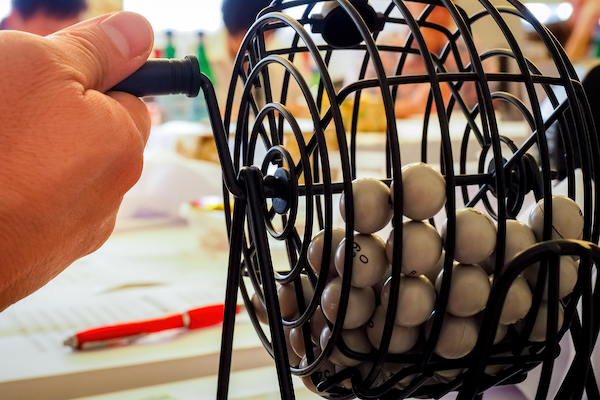 A teacher rotates a basket of bingo balls, as his students focus on their bingo sheets in the background.