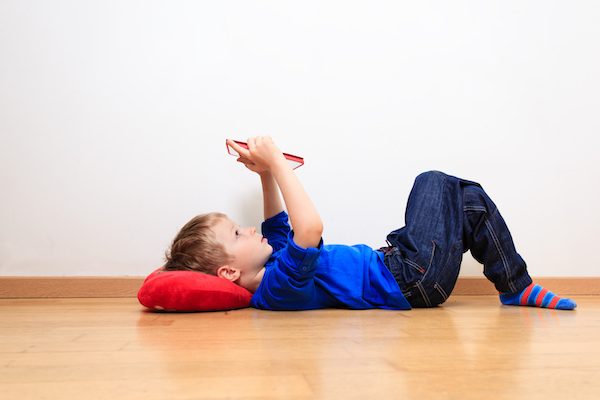 A child lies on the floor, holding up his tablet computer over his face while resting his head on a red pillow.