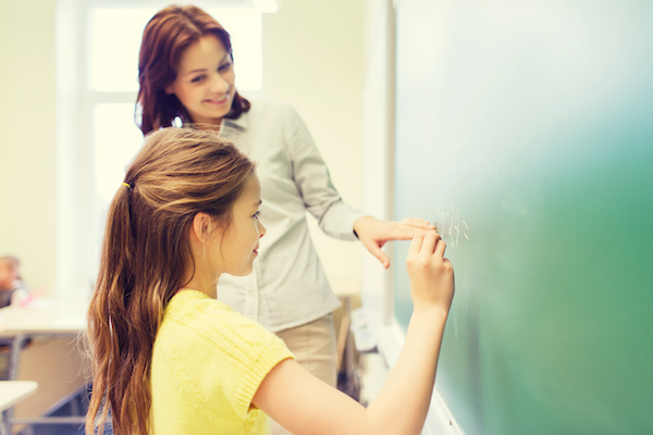 A teacher and young elementary student stand at a blackboard, the teacher encouraging the student as she writes an equation onto the board.