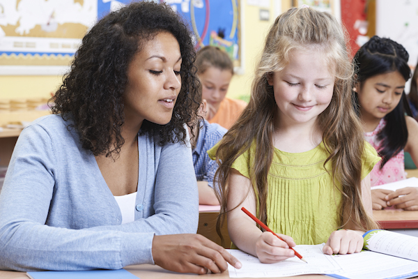 A teacher sits beside her elementary-age students, pointing to her notebook as the student writes something in it.