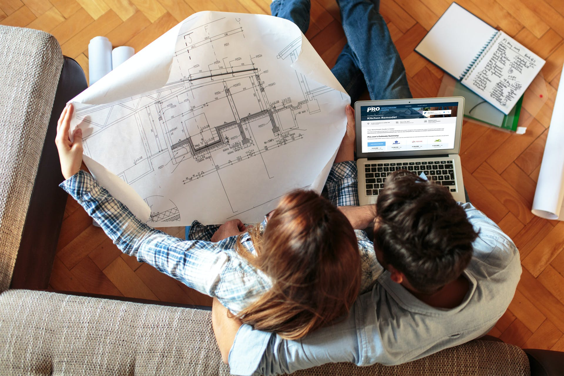 Homeowners reviewing construction estimates from general contractors next to architectural drawing