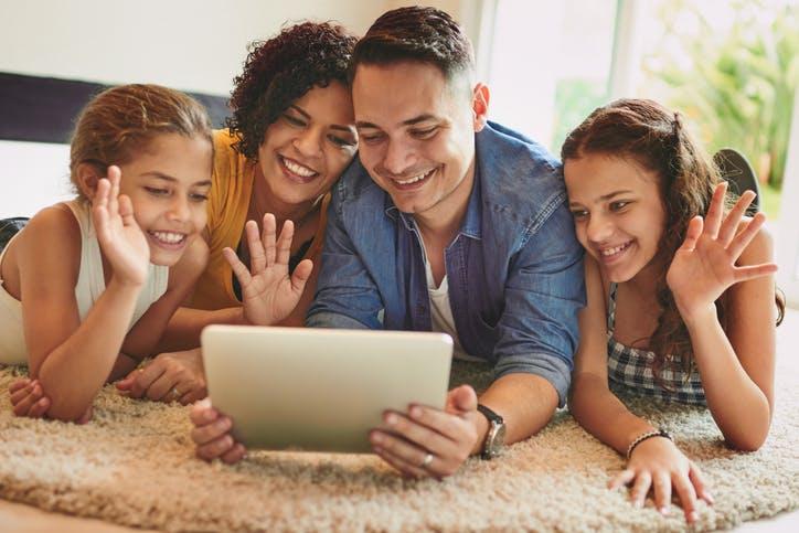 Família deitada no chão fazendo video-chamada pelo tablet