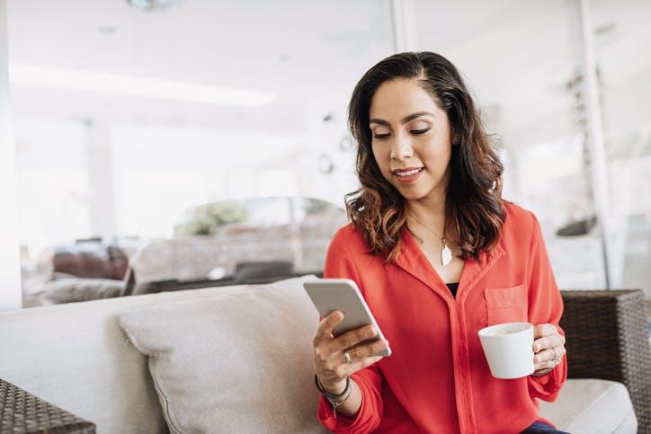 Mulher tomando café e vendo o celular