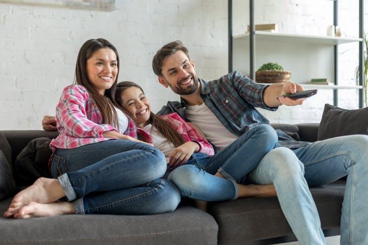 Família sorrindo assistindo à televisão