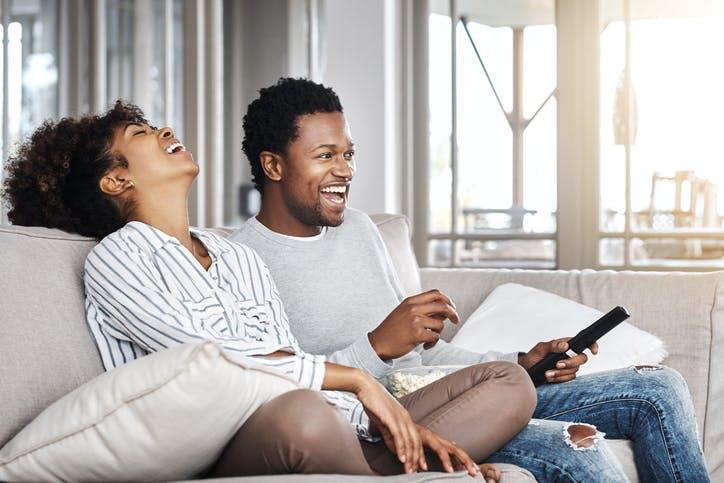 Casal sorrindo e assistindo TV