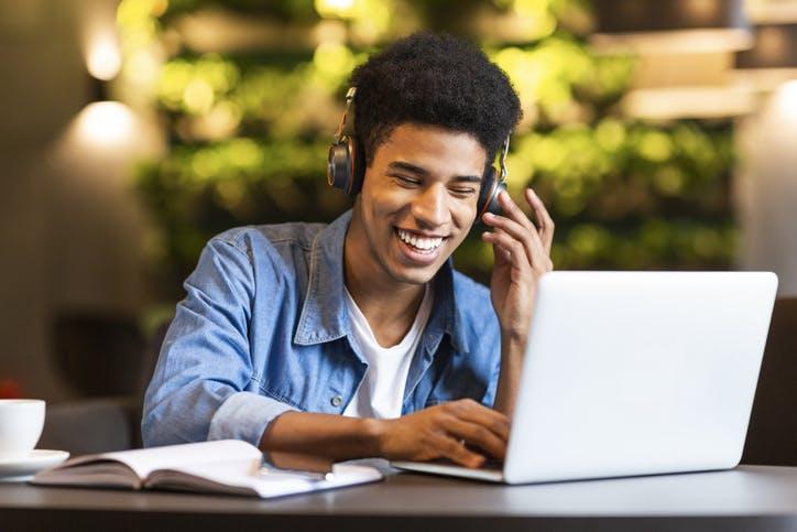 Menino usando o notebook e escutando música em seu head phone com a Claro Internet