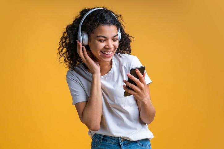 Menina ouvndo musica e olhando o celular