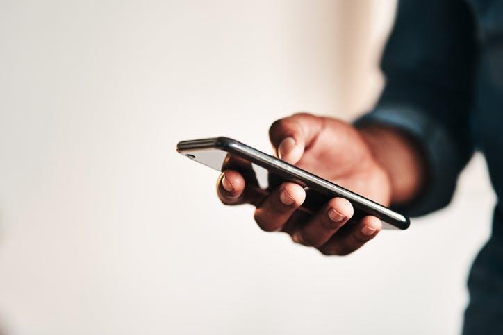 Homem com celular na mão digitando o número do atendimento Claro