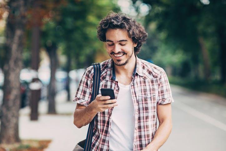 Homem sorrindo e andando na rua mexendo no celular
