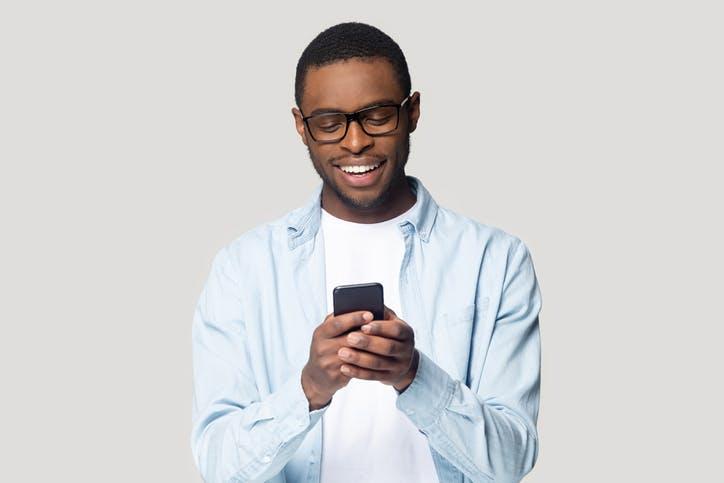 Menino feliz digitando no celular