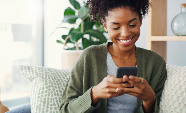 Mulher sentada no sofá, sorrindo e mexendo no celular