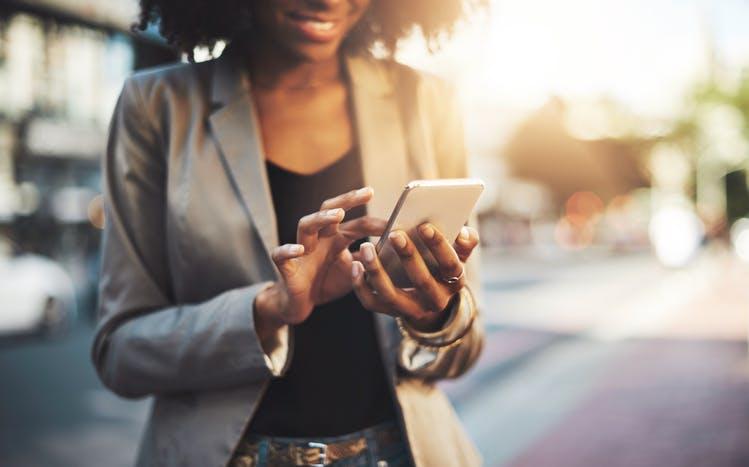 Mulher na rua digitando no celular