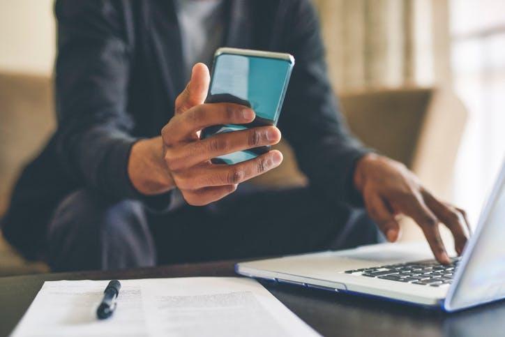 Homem olhando celular e mexendo no notebook