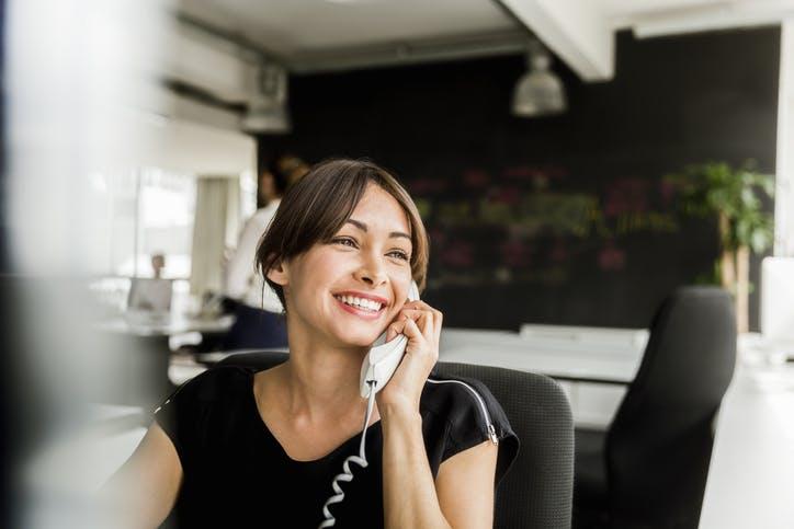 Mulher usando telefone fixo no trabalho