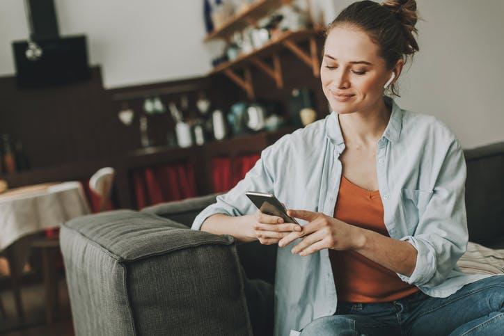 Mulher sentada no sofá, usando fone de ouvido e mexendo no celular