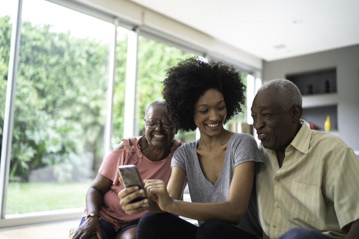 Neta e seus avós sorrindo e olhando para o celular