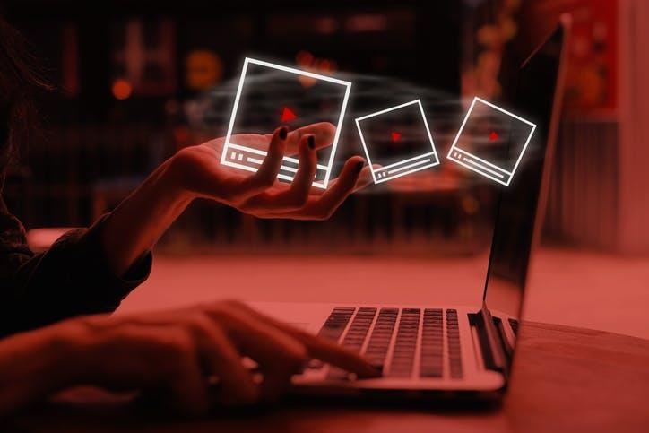 Imagem mulher usando um notebook e ícones que representam vídeos