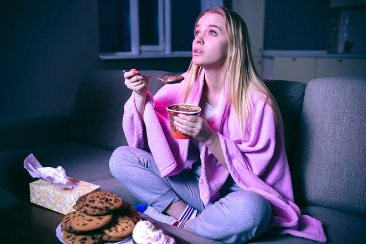 Mulher comendo sorvete de chocolate no sofá e assistindo Claro TV