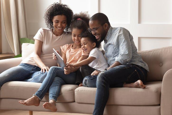 Família sentada no sofá mexendo no tablet