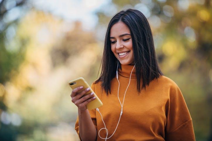 Mulher com celular na mão andando e escutando música em seu fone de ouvido