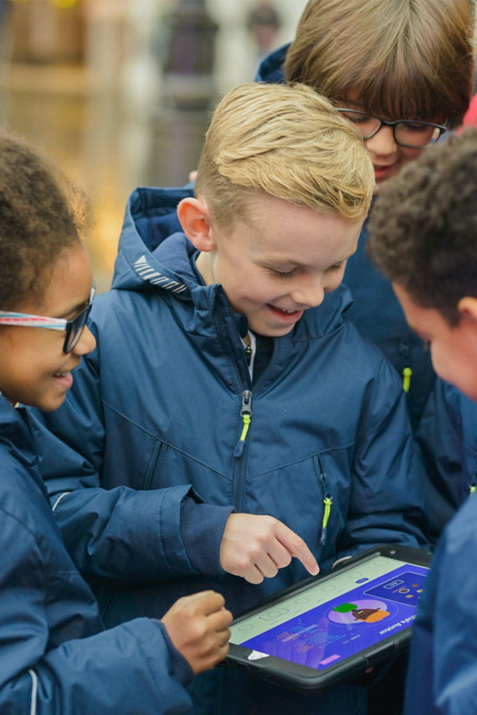 Four young people gathered around an iPad, creating an avatar.