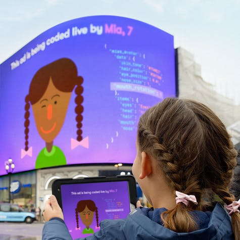 Young person holding an iPad displaying an avatar and computer code, the iPad display mirrored onto the large display at Piccadilly circus.