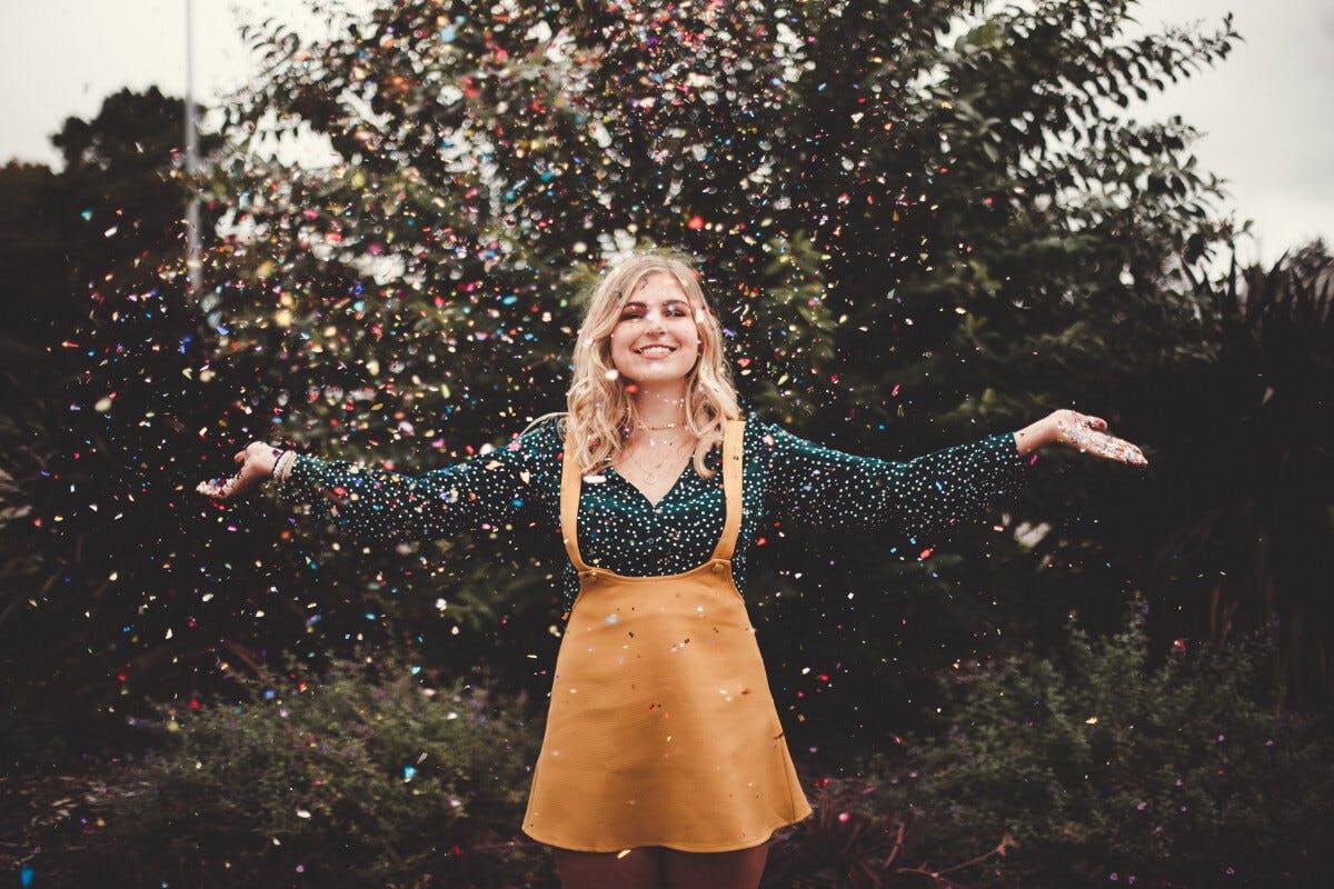 Positiv denken: Glückliche Frau wirft Confetti