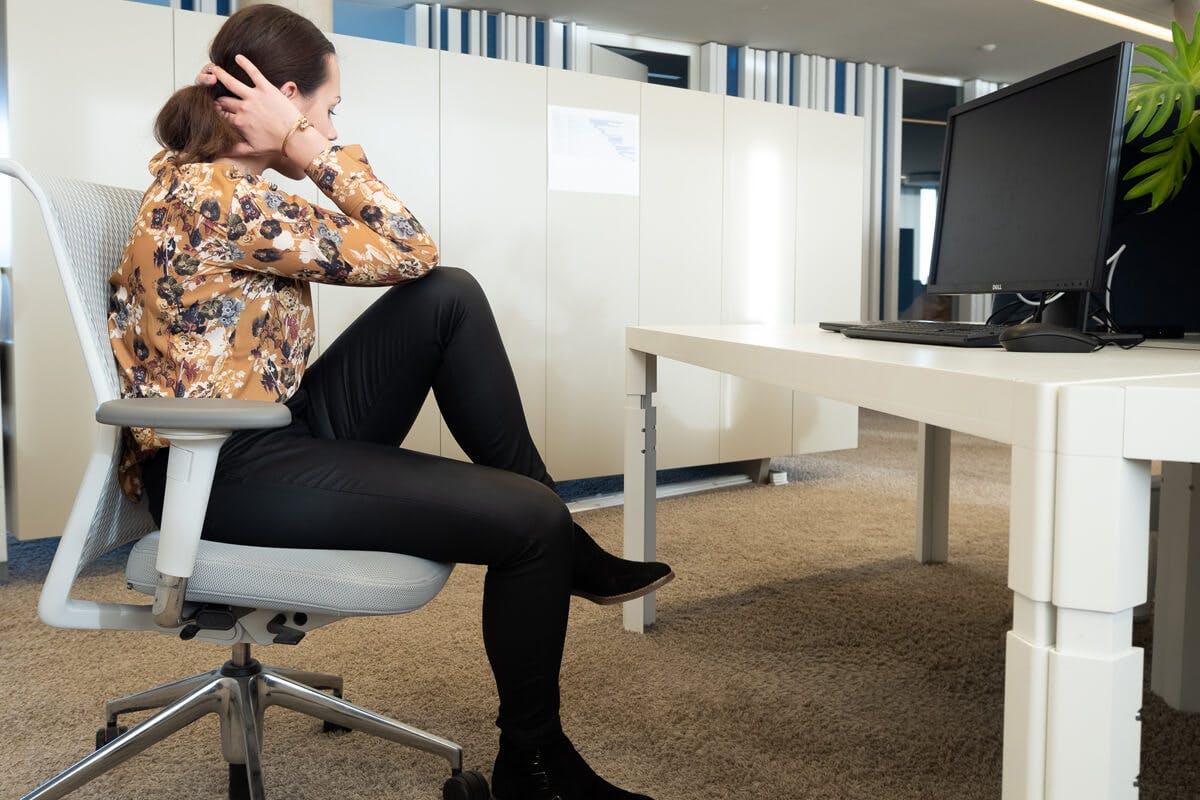 Frau macht Bauchmuskel-Training am Schreibtisch